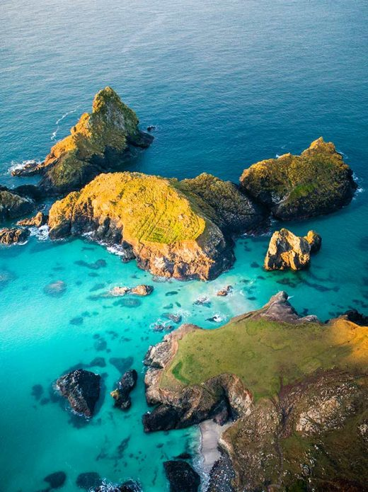 Sunrise at high tide at Kynance Cove on the Lizard Peninsula in Cornwall, England.