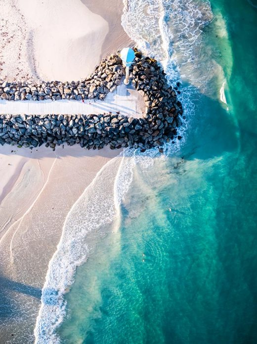 A Drone photo looking down on the city beach jetty in Perth western Australia at sunrise now available for print on canvas, fine art, acrylic and aluminium